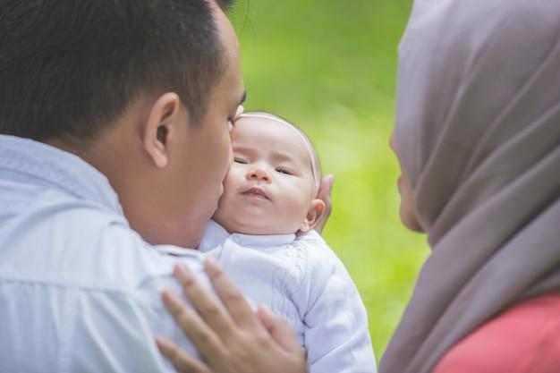 Pai e mãe com seu bebê recém-nascido no parque. Foto Premium