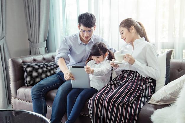 Pai e mãe ensinando as crianças a fazerem o dever de casa em casa, a família asiática é feliz. Foto Premium