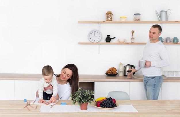 Pai e mãe na cozinha com criança e cópia espaço Foto gratuita