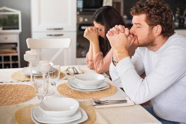 Pai e mãe rezando juntos em casa Foto gratuita