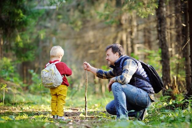 Pai e seu filho bebê andando durante as atividades de caminhadas na floresta de outono ao pôr do sol Foto Premium