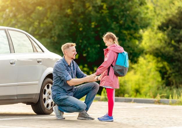 Pai encontrando garotinha depois das aulas no estacionamento Foto Premium