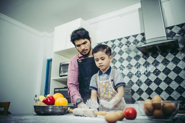 Pai ensina seu filho a cozinhar na cozinha em casa. conceito de família. Foto gratuita