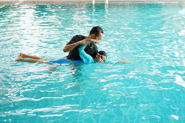 Pai ensinando filha a nadar em uma piscina Foto Premium