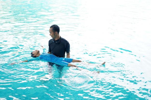 Pai ensinando filha a nadar Foto Premium