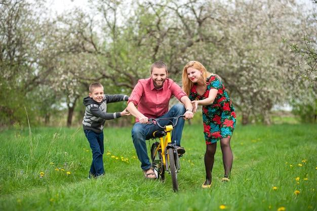 Pai ensinando filho a andar de bicicleta pelo seu exemplo Foto Premium