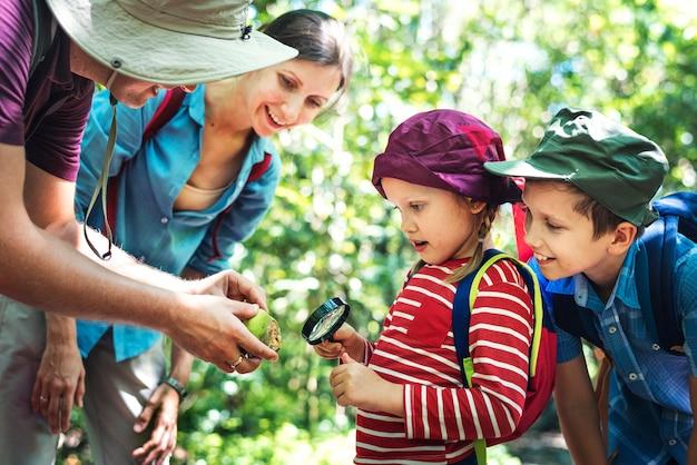 Pai ensinando sua filha a usar uma lupa Foto gratuita