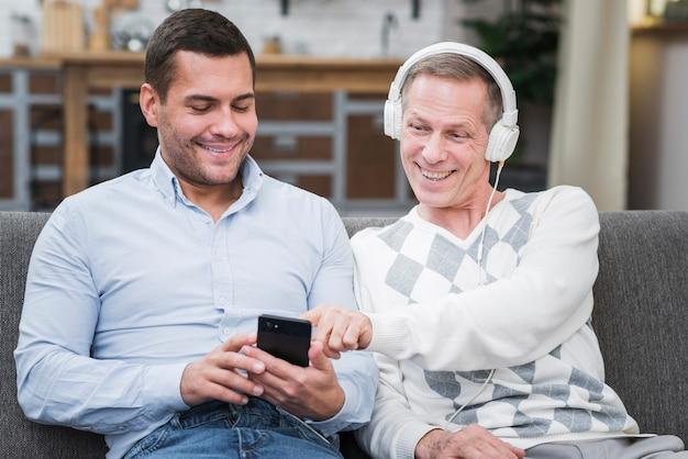 Pai, escolhendo música no telefone do filho Foto gratuita