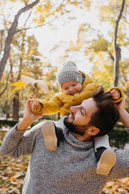 Pai feliz com seu bebê ao ar livre Foto gratuita