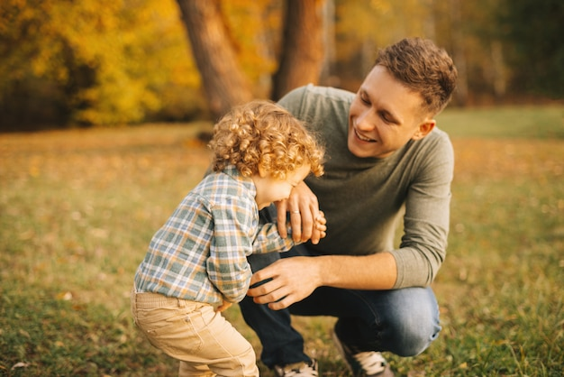 Pai feliz com seu filho pequeno sorrindo ao ar livre no parque ao pôr do sol, se divertindo juntos Foto Premium