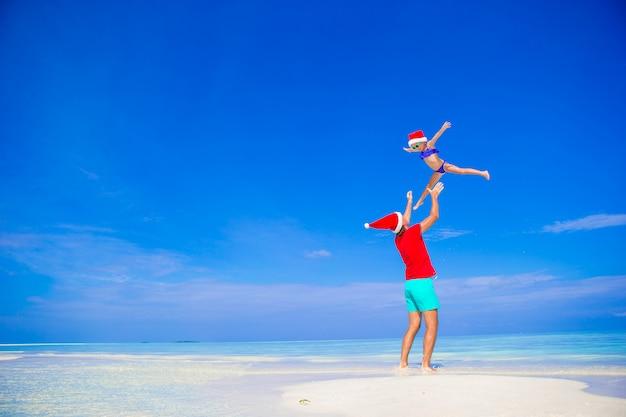 Pai feliz e sua adorável filha pequena no chapéu de papai noel na praia tropical Foto Premium