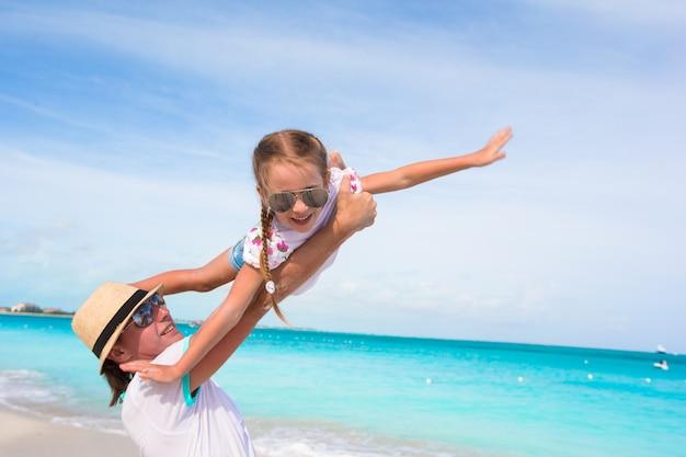 Pai feliz se divertir com sua menina bonita durante as férias de praia Foto Premium