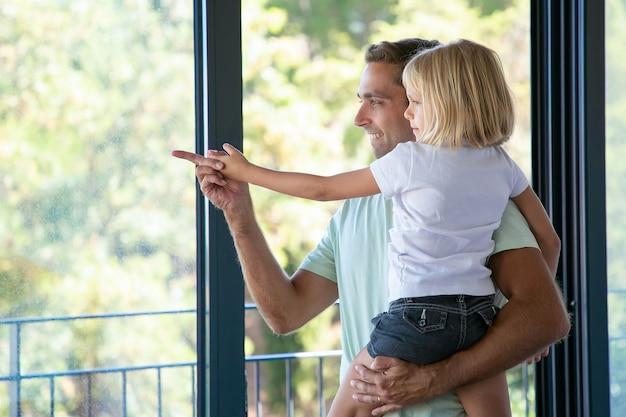Pai feliz segurando a filha fofa e apontando para algum lugar Foto gratuita