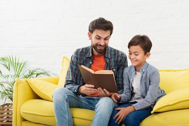 Pai filho, lendo um livro Foto gratuita