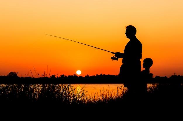 Pai filho, pesca, em, a, rio, pôr do sol, backgrond Foto Premium