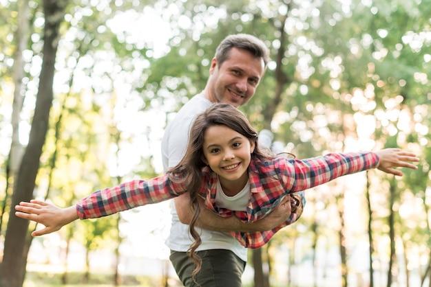 Pai forte, carregando sua filha no parque Foto gratuita