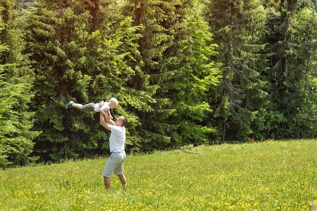 Pai joga filho bebê no prado verde Foto Premium