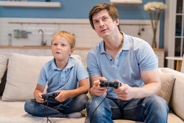 Pai jogando videogame junto com filho Foto gratuita