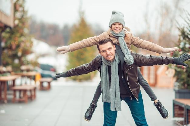 Pai jovem e adorável menina se divertir na pista de patinação ao ar livre Foto Premium