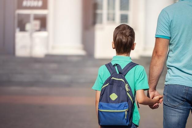 Pai leva um menino de escola de criança andam de mãos dadas. pai e filho com mochila nas costas. Foto Premium