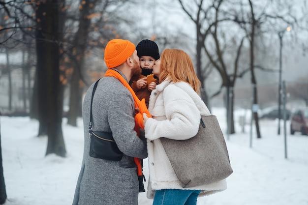 Pai mãe e bebê no parque no inverno Foto gratuita