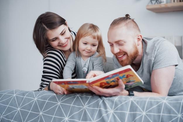 Pai, mãe e filha lendo o livro infantil em um sofá na sala de estar. família grande e feliz ler um livro interessante em um dia festivo. os pais amam seus filhos Foto Premium