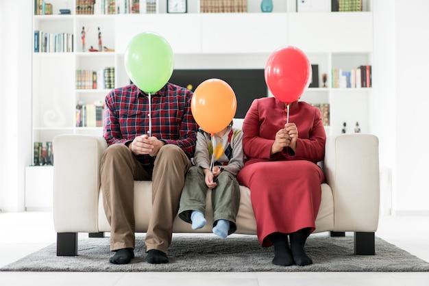 Pai mãe e se escondendo atrás de balões em casa Foto Premium