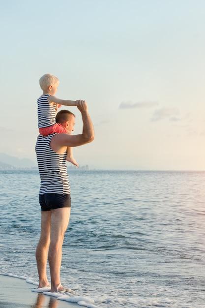 Pai mantém seu filho nos ombros à beira-mar. hora do sol Foto Premium