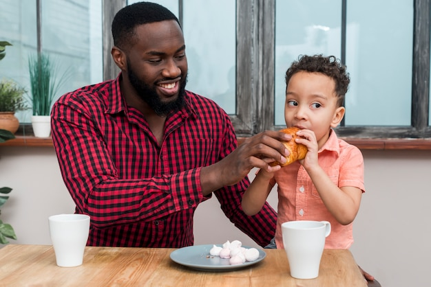 Pai negro, alimentando o filho com croissant Foto gratuita
