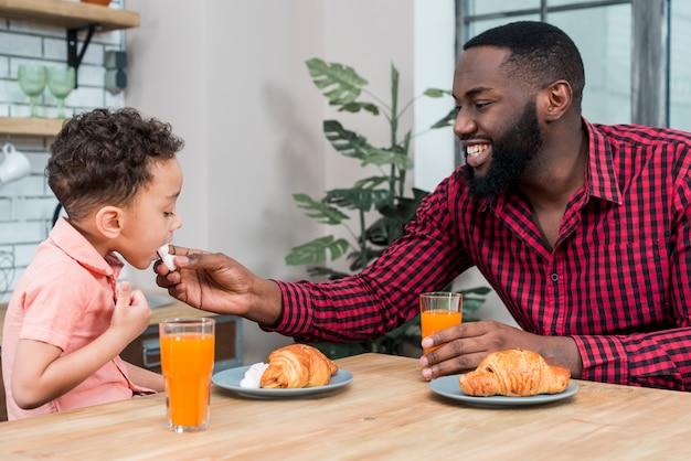 Pai negro, alimentando o filho com doces Foto gratuita