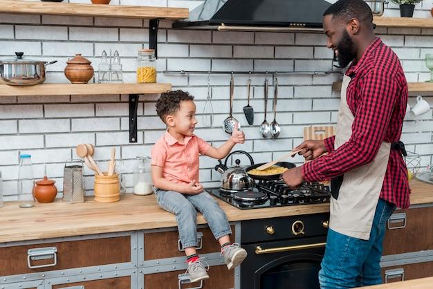 Pai negro cozinhar comida enquanto filho aparecendo polegar Foto gratuita
