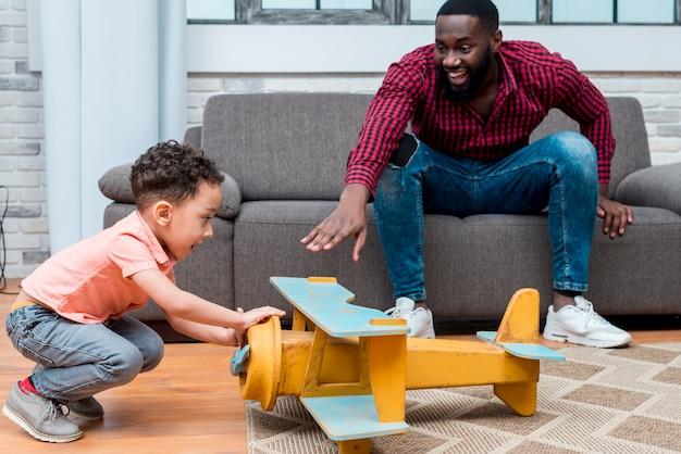Pai negro e filho brincando com o avião grande brinquedo Foto gratuita
