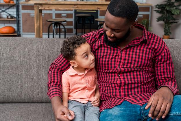 Pai e filho conversando sentados no sofá