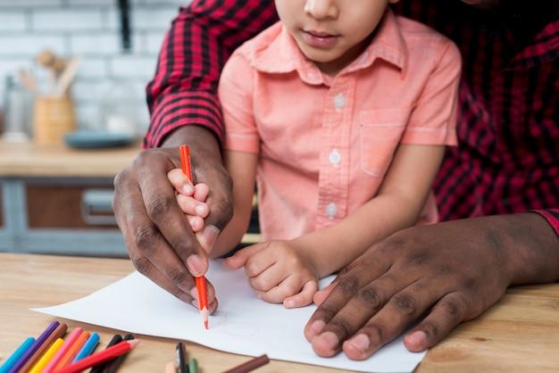 Pai negro e filho desenho em papel Foto gratuita