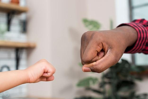 Pai negro e filho pequeno, batendo os punhos Foto gratuita