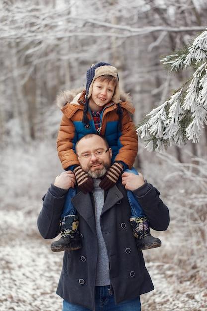Pai novo barbudo e filho pequeno na caminhada na floresta de inverno. rapaz senta-se nos ombros do homem. férias de natal Foto Premium