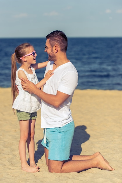 Pai novo e sua filha pequena bonito em vidros de sol. Foto Premium