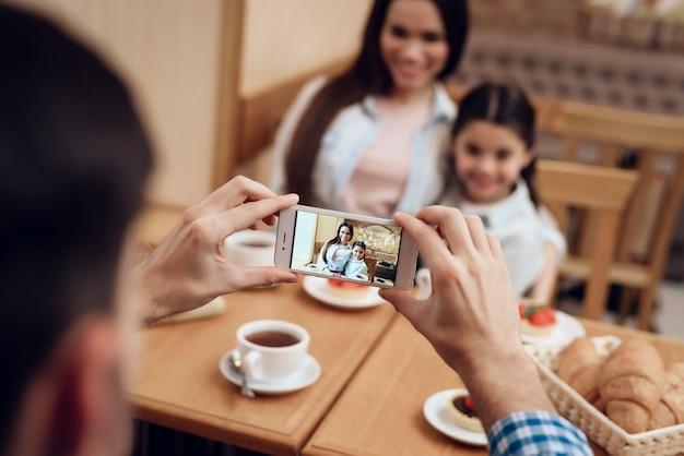 Pai novo que toma a foto da família no bar. Foto Premium