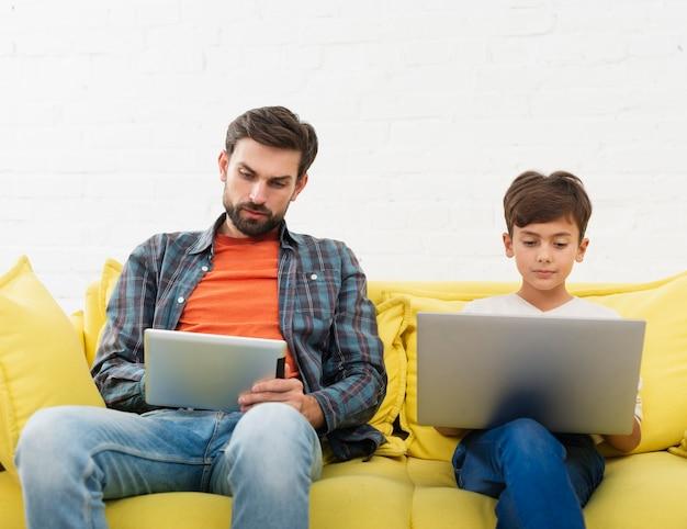 Pai olhando no tablet e filho trabalhando no laptop Foto gratuita