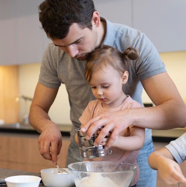 Pai próximo ajudando criança com farinha Foto gratuita