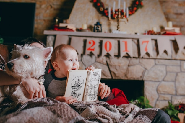 Pai que prende um livro que seu bebê está olhando e tocando Foto gratuita