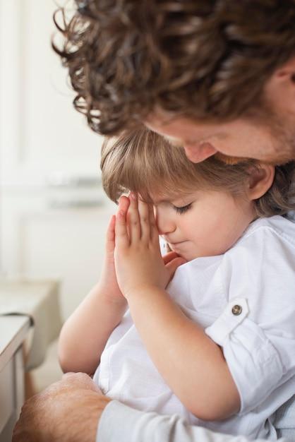 Pai rezando junto com a criança Foto gratuita