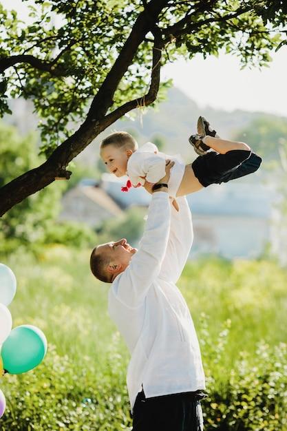 Pai, segura, pequeno, filho, em, camisa bordada, em, seu, braços, ficar, sob, árvore verde Foto gratuita