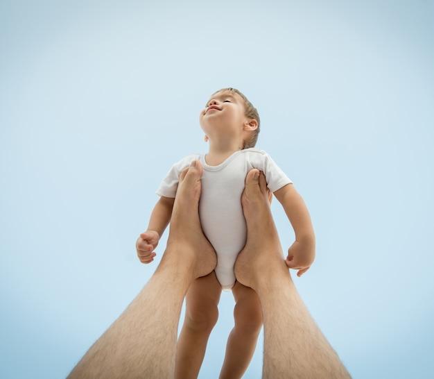 Pai segurando bebê filho nas pernas no ar Foto Premium