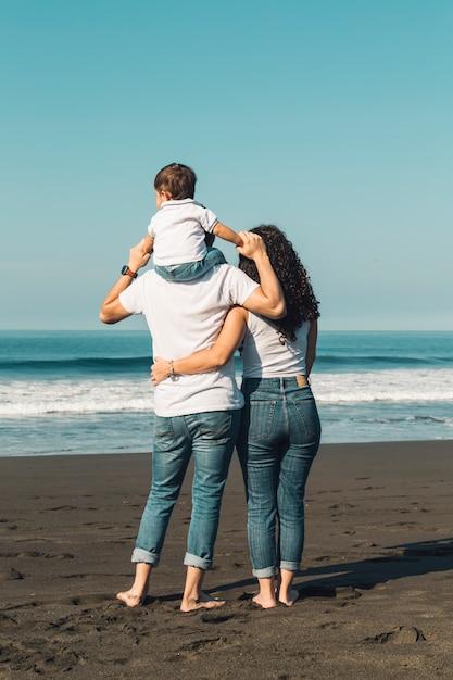 Pai, segurando, bebê, ligado, pescoço, e, abraçando, com, esposa, ligado, praia Foto gratuita