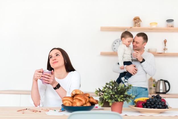 Pai segurando filho enquanto a mãe está à mesa na cozinha Foto gratuita