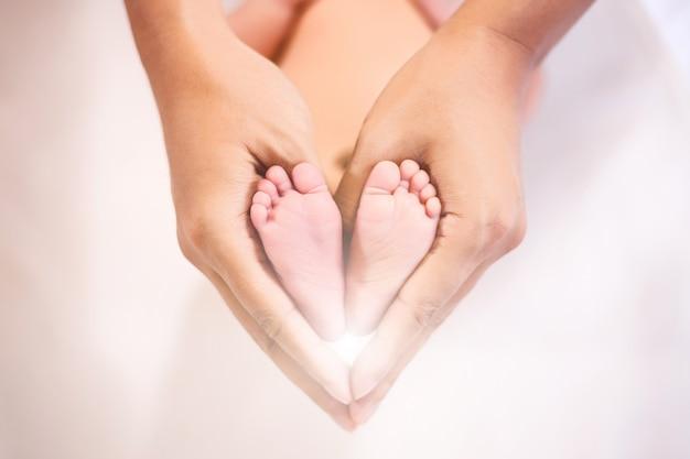 Pai segurando nos pés do bebê recém-nascido. Foto Premium