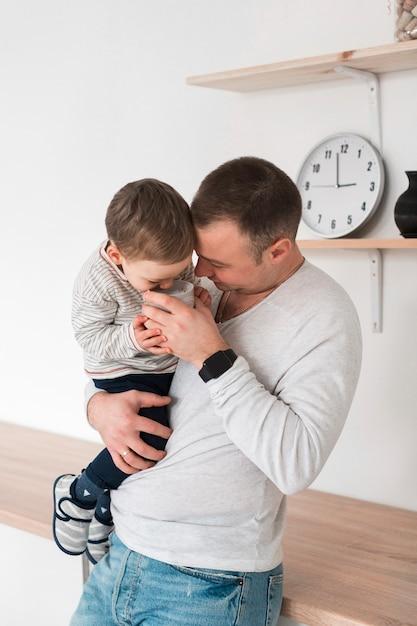 Pai segurando seu filho e caneca na cozinha Foto gratuita