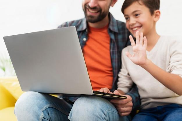 Pai segurando um laptop e criança saudando Foto gratuita
