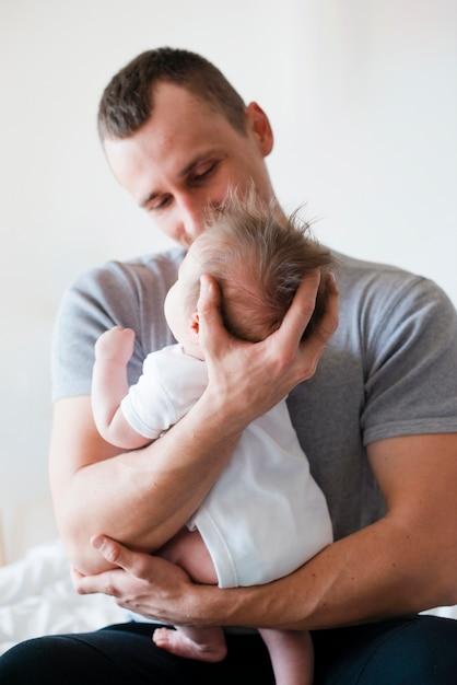 Pai, sentando, e, abraçar, bebê Foto gratuita